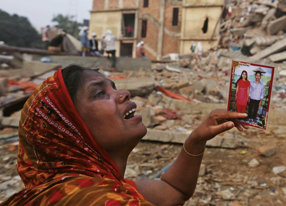 Une femme brandit face aux ruines une photo d'elle et de son mari disparu.