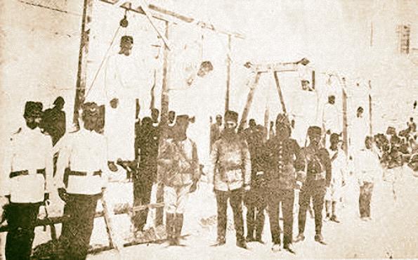 1915: sur une place publique Alep, des soldats turcs posent devant des Arméniens pendus