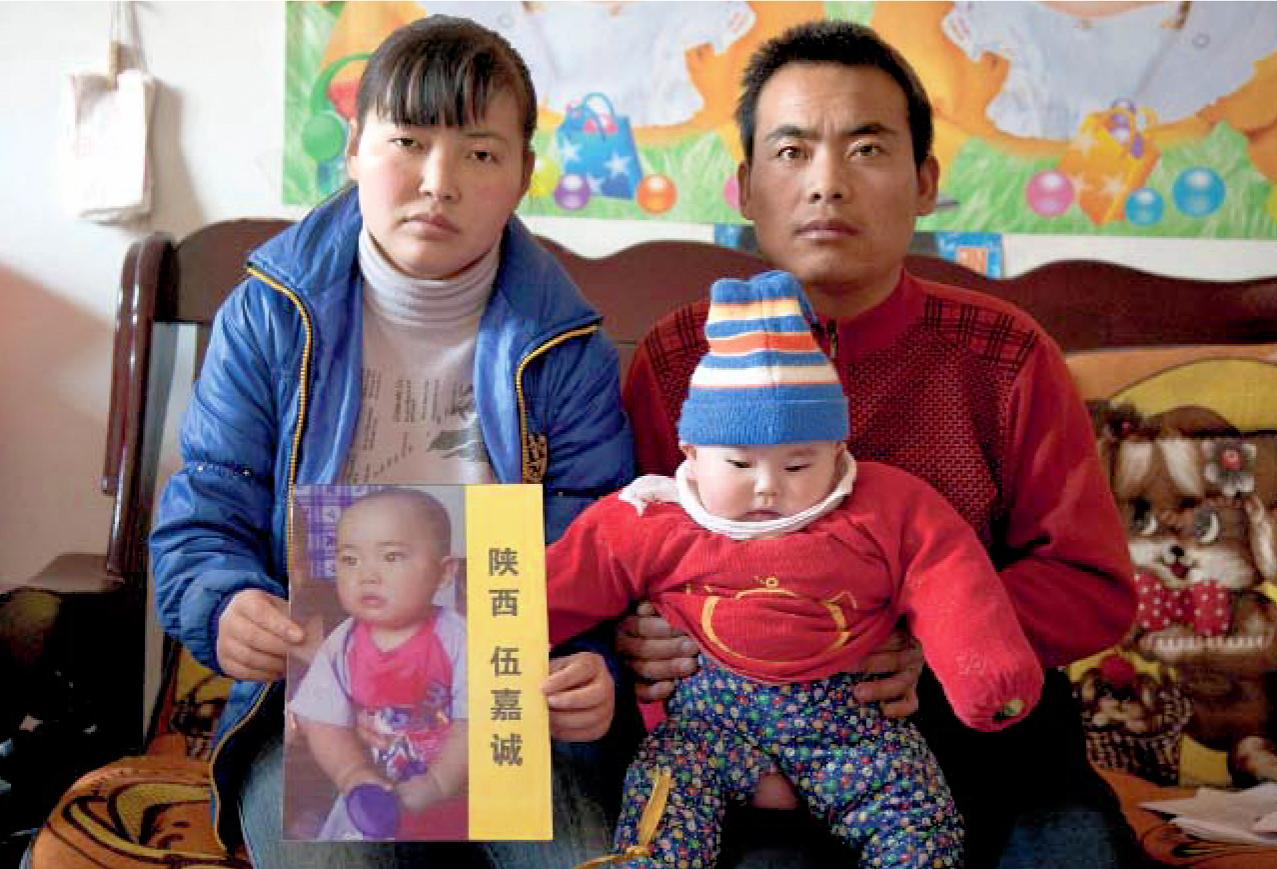 Les parents et la sœur de Jiacheng, dans leur maison près de Xian, en 2011. Sur les genoux de la mère, une photo du petit garçon, enlevé le 10 décembre 2008 à l'âge de 1 an.