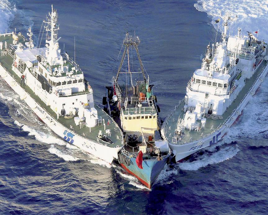 Bateau de pêche, avec à bord des activistes chinois, coincé par deux garde-côtes japonais, le 15 août 2012, près de l'archipel des Senkaku, en mer de Chine orientale