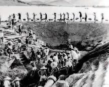 En 1958, dans la commune de Weixing, au bord d'un lac, pendant le Grand Bond en avant, des Chinois creusent un réservoir pour irriguer les champs.